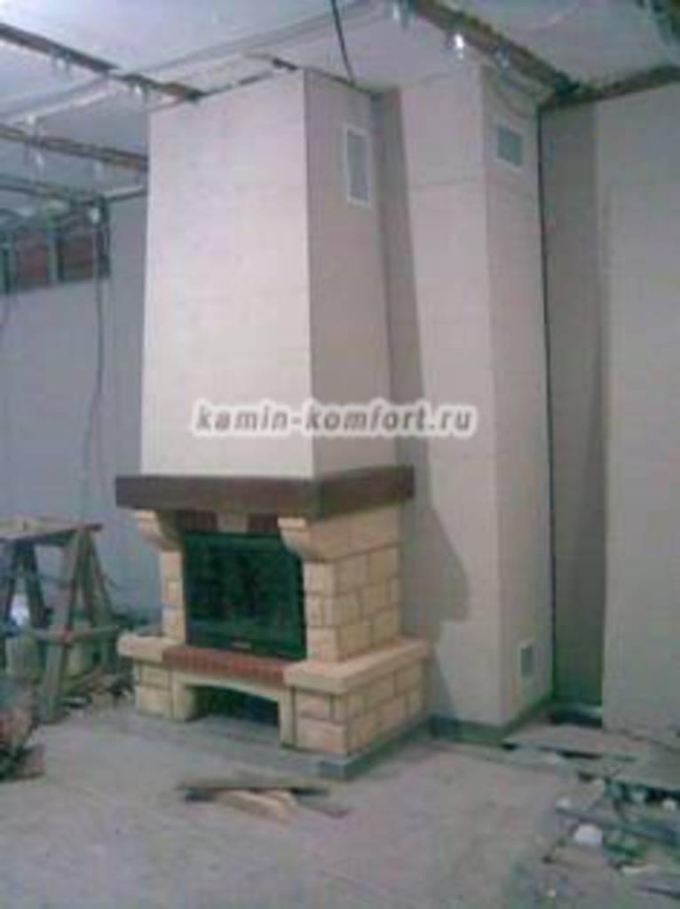 Фото Пристенный камин с деревянной балкой на объекте